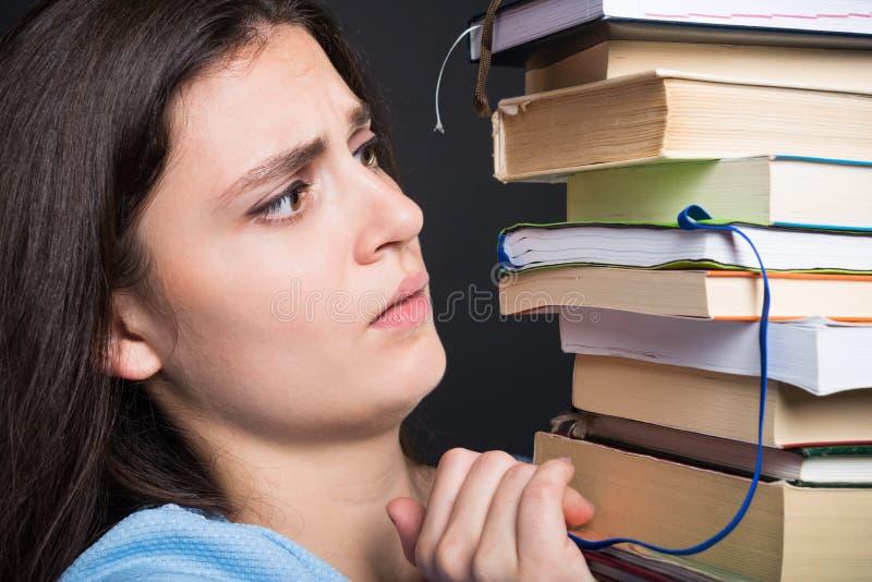Estudiante joven triste que sostiene muchos libros fotos de archivo libres de regalías