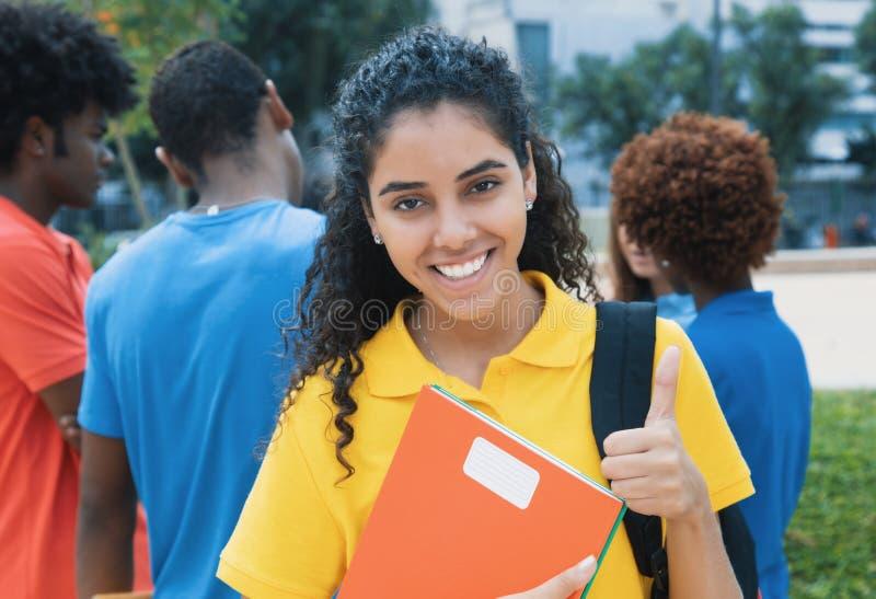 Estudiante latino lindo con el grupo de otros estudiantes foto de archivo