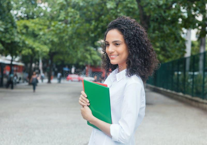 Estudiante latino lindo con el pelo rizado y la camisa blanca foto de archivo
