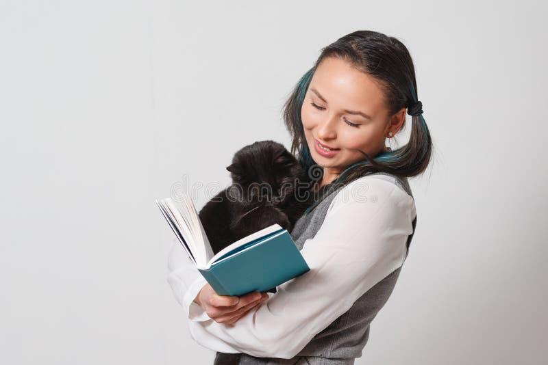 Estudiante lindo de la chica joven con un gato divertido en sus brazos que lee un libro en fondo ligero foto de archivo libre de regalías