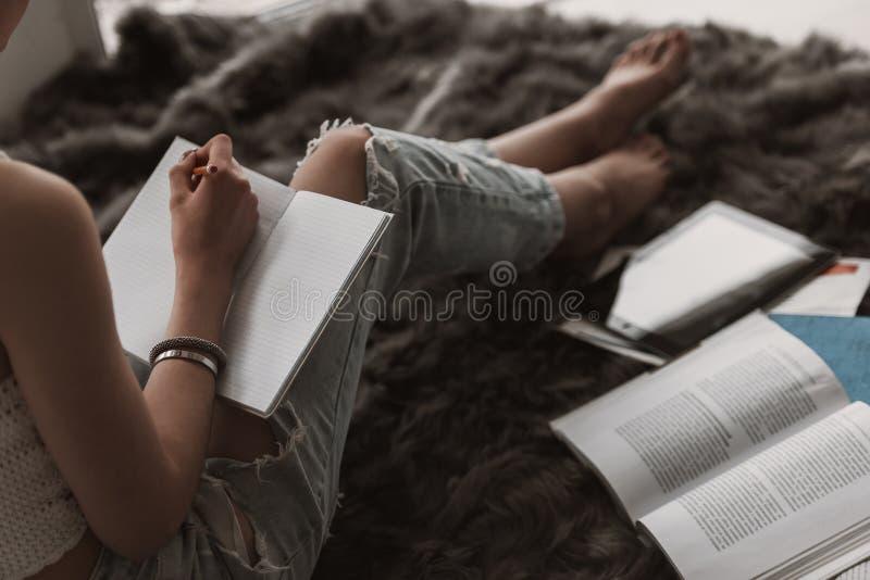 Estudiante lindo joven Doing Homework en cama imágenes de archivo libres de regalías