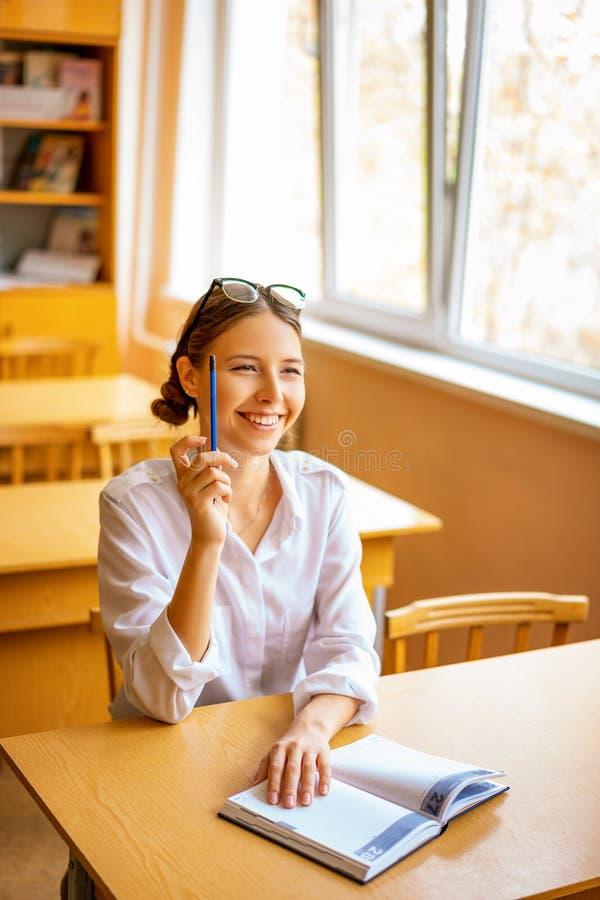 Estudiante lindo que se sienta con un cuaderno en el escritorio por la ventana, visión pensativa imágenes de archivo libres de regalías