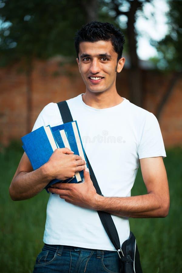 Estudiante masculino árabe con los libros al aire libre imágenes de archivo libres de regalías