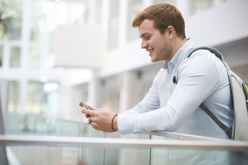 Estudiante masculino adulto que usa smartphone en interior de la universidad foto de archivo