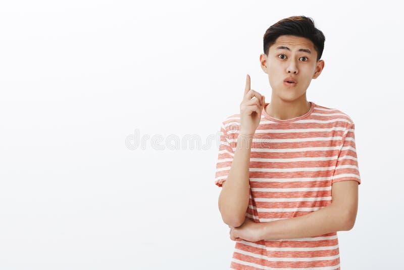 Estudiante masculino asiático creativo joven que comparte ideas durante el proyecto del grupo que aumenta el dedo índice en el ge fotografía de archivo libre de regalías