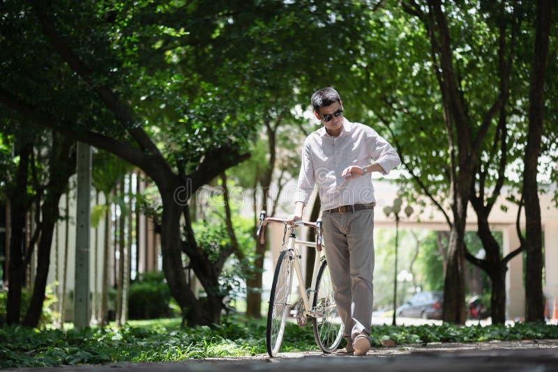 Estudiante masculino asiático que comprueba tiempo encendido en su reloj con el cycl foto de archivo libre de regalías