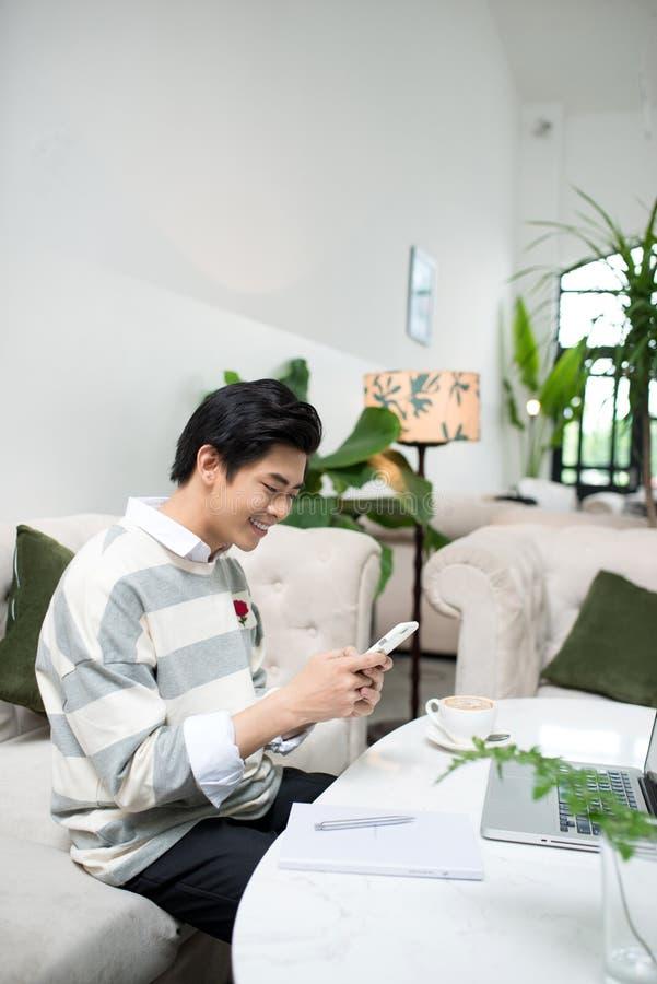 Estudiante masculino asiático que manda un SMS por el teléfono mientras que se sienta en el café sh fotografía de archivo libre de regalías