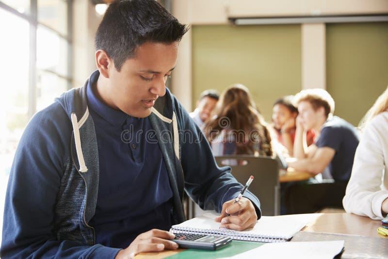 Estudiante masculino With Calculator Working de la High School secundaria en el escritorio imagenes de archivo