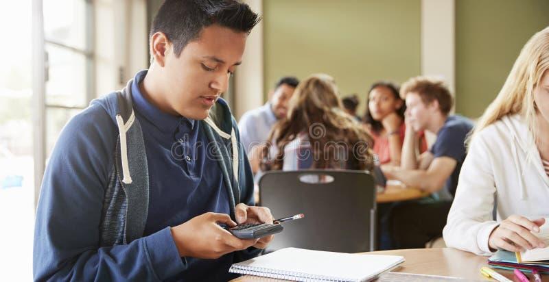 Estudiante masculino With Calculator Working de la High School secundaria en el escritorio fotos de archivo libres de regalías