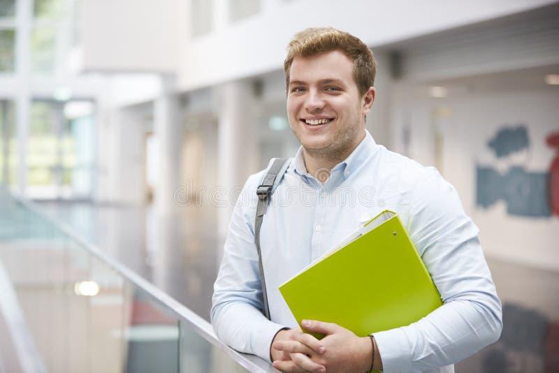 Estudiante masculino caucásico sonriente en el edificio moderno de la universidad imagenes de archivo