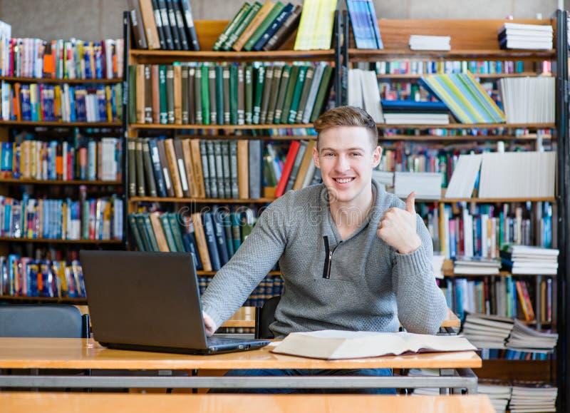 Estudiante masculino con el ordenador portátil que muestra los pulgares para arriba en la biblioteca de universidad foto de archivo