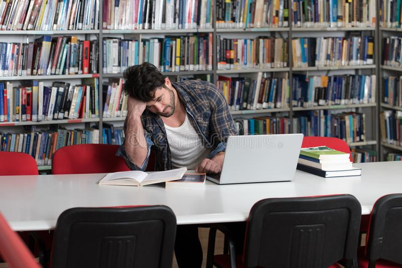Estudiante masculino confuso Reading Many Books para el examen imagen de archivo