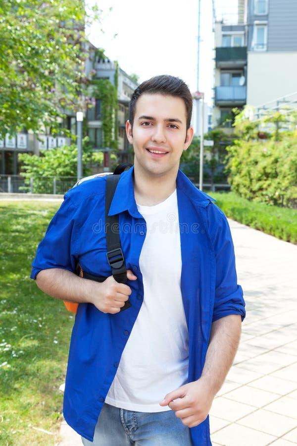 Estudiante masculino en campus que camina en la cámara imágenes de archivo libres de regalías