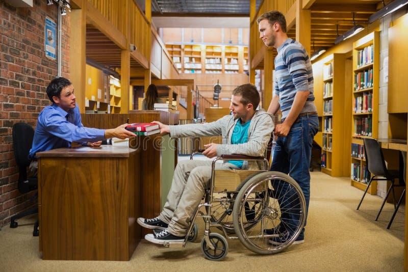 Estudiante masculino en silla de ruedas en el contador de la biblioteca imagen de archivo
