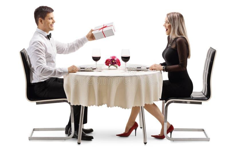 Estudiante masculino en un café que da a una rosa roja a una hembra enojada imagen de archivo