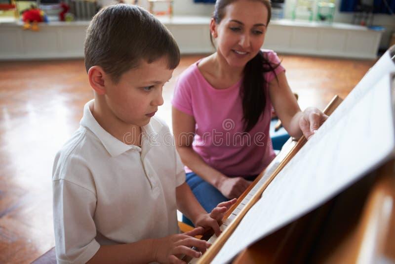 Estudiante masculino Enjoying Piano Lesson con el profesor imagen de archivo
