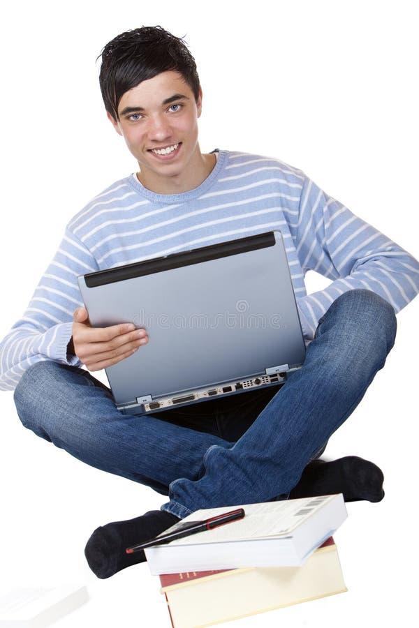 Estudiante masculino feliz que se sienta con la computadora portátil en suelo imagen de archivo libre de regalías