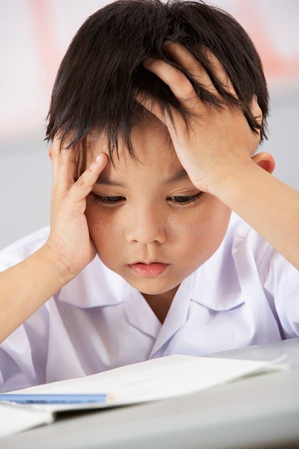 Estudiante masculino infeliz que trabaja en el escritorio foto de archivo