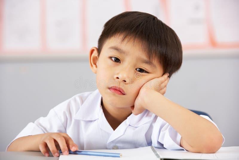 Estudiante masculino infeliz que trabaja en el escritorio en escuela foto de archivo