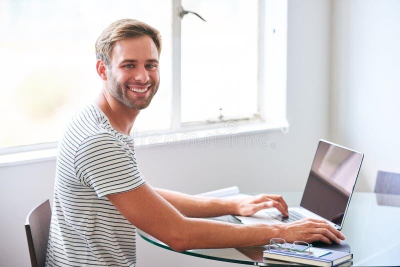 Estudiante masculino joven hermoso que sonríe en la cámara asentada detrás del ordenador portátil imágenes de archivo libres de regalías