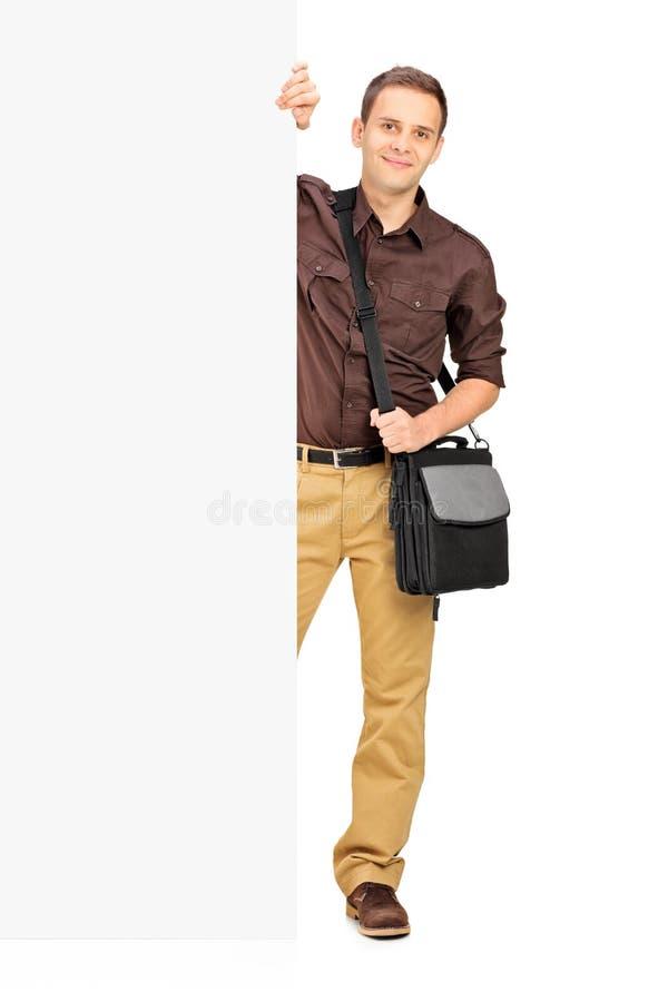 Estudiante masculino joven que se coloca detrás de un panel fotos de archivo libres de regalías