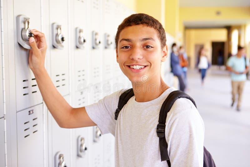 Estudiante masculino Opening Locker de la High School secundaria fotos de archivo