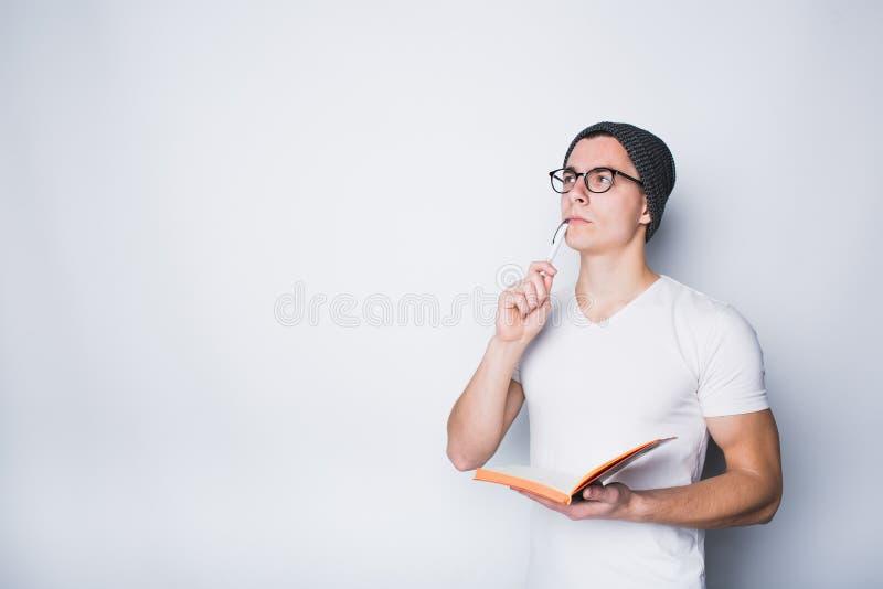 Estudiante masculino pensativo que sostiene el cuaderno y que parece para arriba aislado en un fondo blanco fotografía de archivo libre de regalías