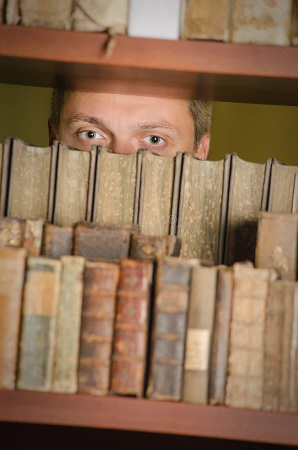 Estudiante masculino que mira a escondidas a través del estante de la biblioteca fotos de archivo libres de regalías