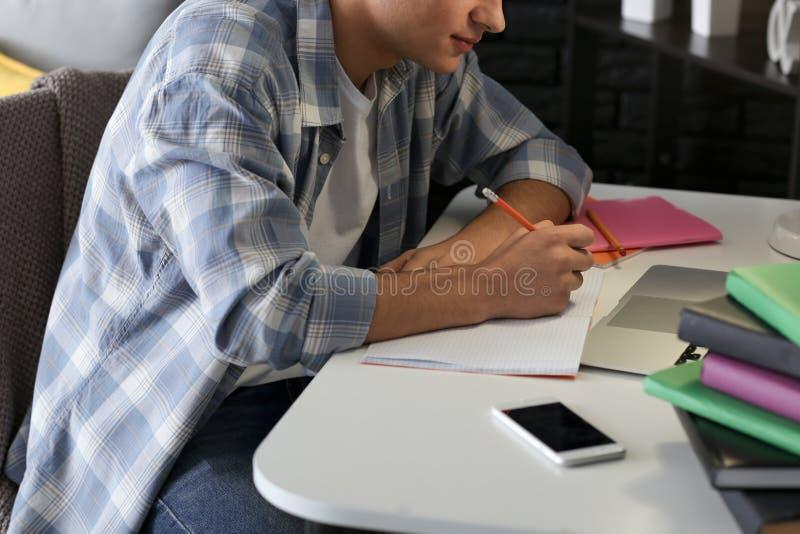 Estudiante masculino que se prepara para el examen en casa imagen de archivo