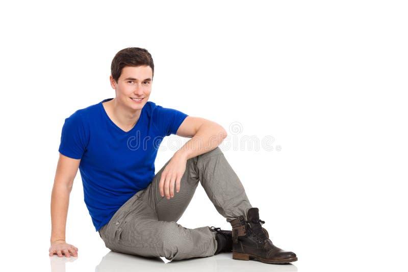 Estudiante masculino que se sienta en el piso. imagenes de archivo