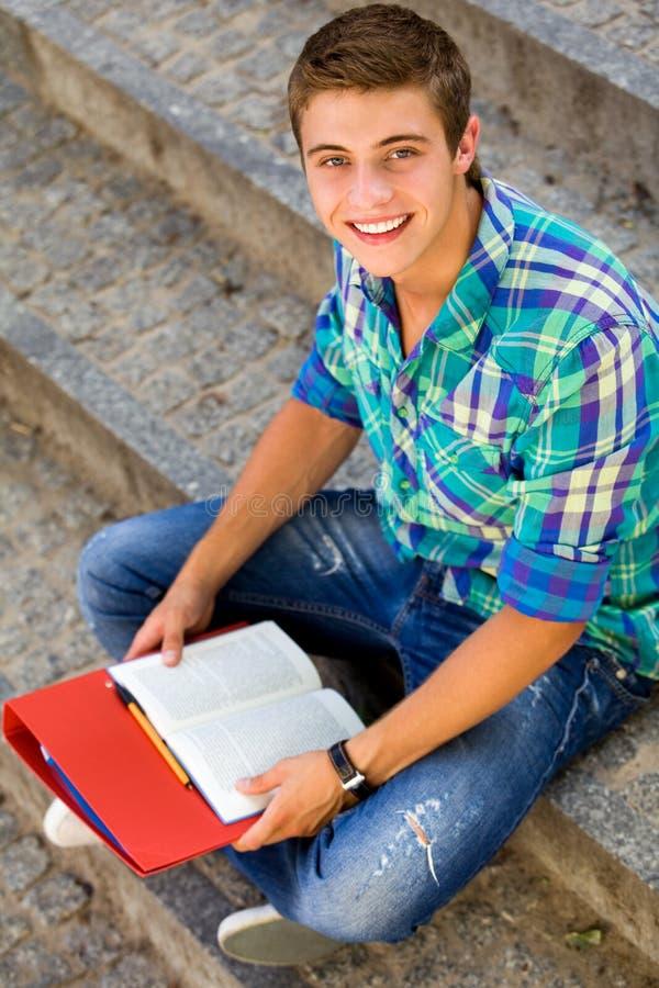Estudiante masculino que se sienta en las escaleras imagen de archivo libre de regalías