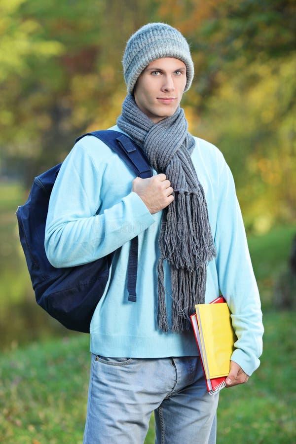 Estudiante masculino que sostiene los libros en un día frío en parque imágenes de archivo libres de regalías