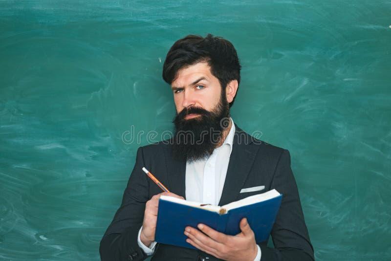 Estudiante masculino serio que estudia en escuela Profesor barbudo joven cerca de la pizarra en sala de clase de la escuela Profe fotografía de archivo