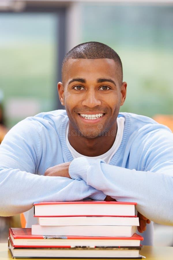 Estudiante masculino Studying In Classroom con los libros fotografía de archivo libre de regalías