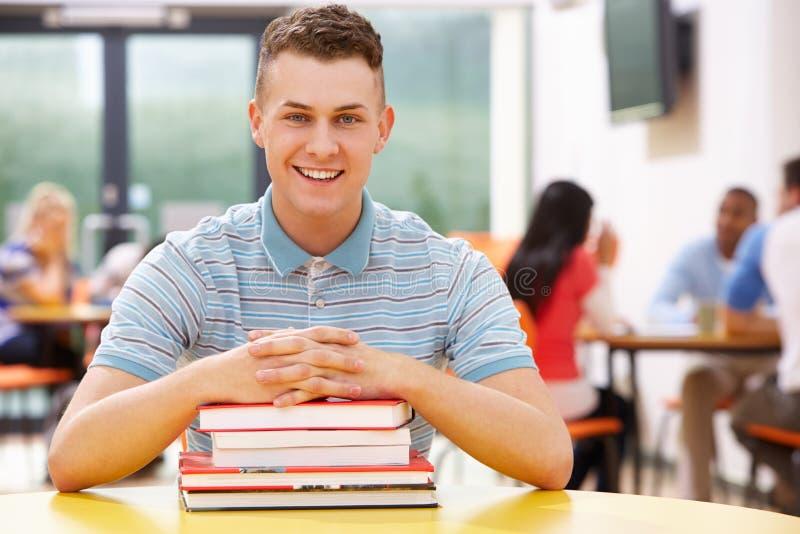 Estudiante masculino Studying In Classroom con los libros imágenes de archivo libres de regalías