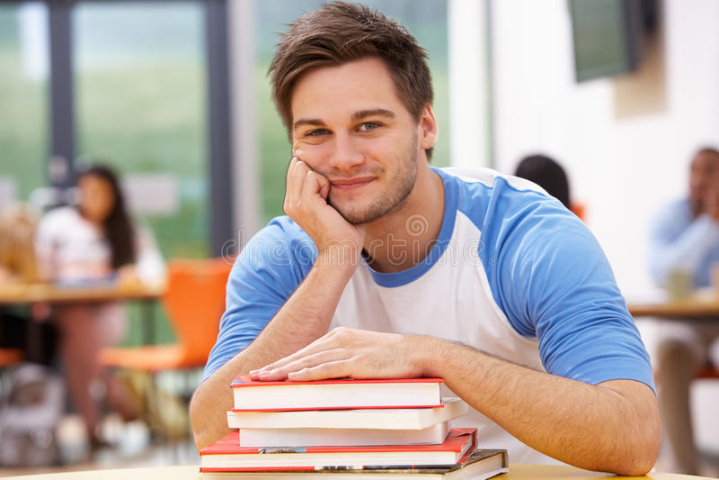 Estudiante masculino Studying In Classroom con los libros imagenes de archivo