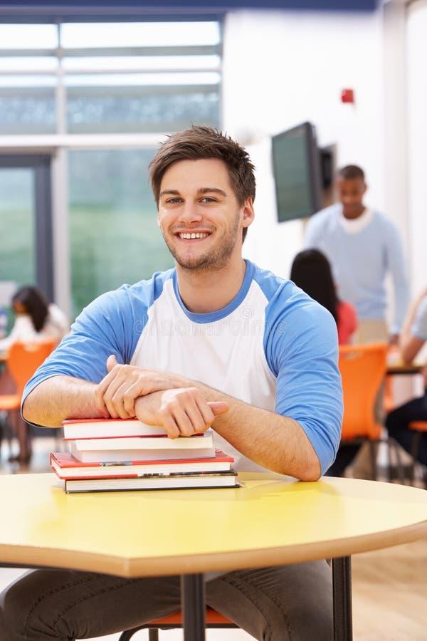 Estudiante masculino Studying In Classroom con los libros imagen de archivo