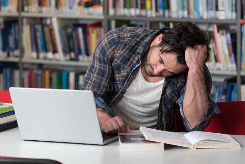Estudiante masculino triste en la biblioteca de universidad fotografía de archivo libre de regalías