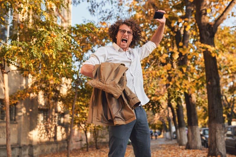 Estudiante masculino u hombre de negocios acertado feliz con el pelo rizado que grita con la expresión que gana, puños bombeados  fotografía de archivo