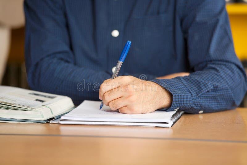Estudiante masculino Writing In Book en la biblioteca foto de archivo