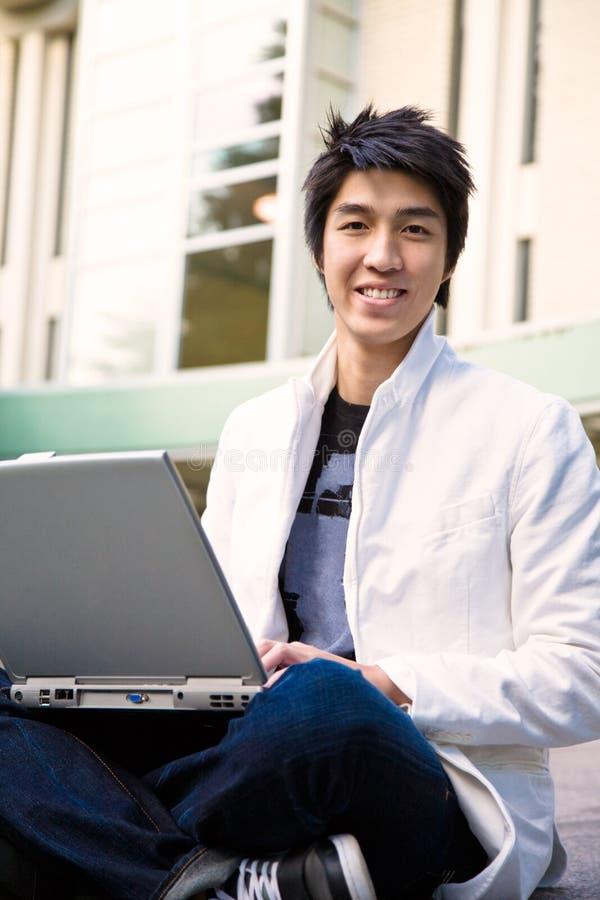 Estudiante masculino y computadora portátil asiáticos fotografía de archivo