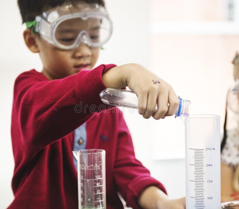 Estudiante Mixing Solution en clase del experimento de la ciencia foto de archivo