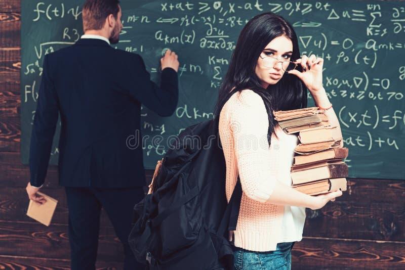 Estudiante moreno atractivo que sostiene sus vidrios mientras que lleva la pila de libros Estudiante universitaria joven en rebec imagen de archivo