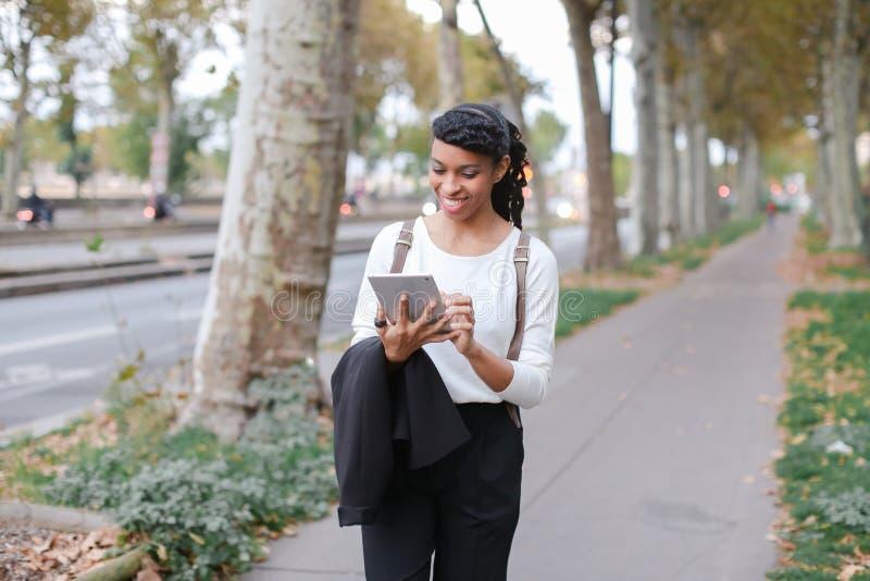 Estudiante negro que usa la tableta y caminando en la calle con los árboles fotos de archivo