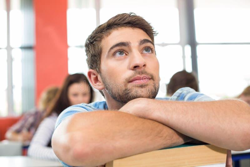 Estudiante pensativo con los libros en sala de clase fotos de archivo