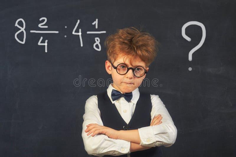 Estudiante pensativo de la escuela primaria en clase fotografía de archivo