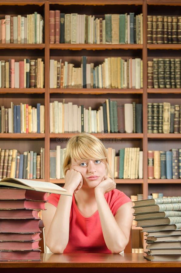 Estudiante preocupante en biblioteca con los codos en la tabla imagen de archivo