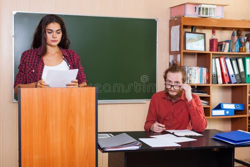 Estudiante Prepare Report Seminar que se coloca en la plataforma en sala de clase, profesor Listen High de la chica joven imagen de archivo