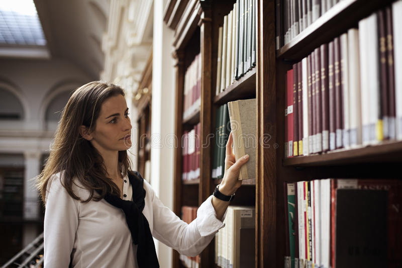 Estudiante que busca un libro en biblioteca. fotos de archivo libres de regalías