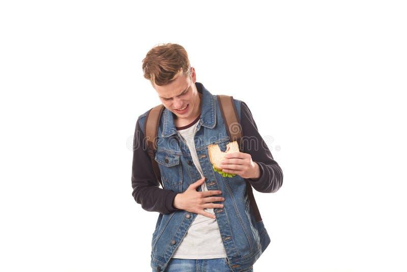 Estudiante que come el bocadillo putrefacto foto de archivo